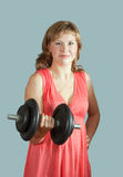 Woman in dress  with barbell Stock Images