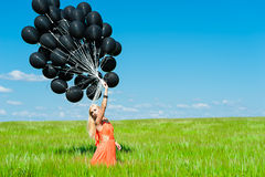 Woman in a dress and black balloons Stock Photography
