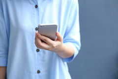 Woman dress blue shirt with using smartphone Stock Image