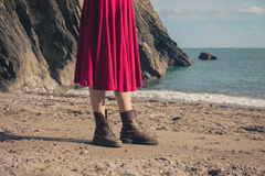 Woman in dress and boots on beach Stock Photography