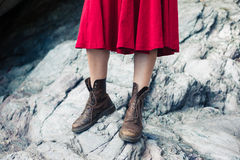 Woman in dress and boots standing on rocks Royalty Free Stock Photos