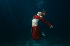 Woman in dress on the bottom underwater. Royalty Free Stock Images