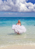 Woman in dress of the bride runs on waves of sea Royalty Free Stock Photos