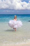 Woman in a dress of bride runs on waves of sea Stock Image