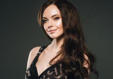 Woman in dress, brunette with long hair over dark background fem. Ale portrait. Studio shot stock photo