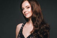 Woman in dress, brunette with long hair over dark background fem. Ale portrait. Studio shot royalty free stock image