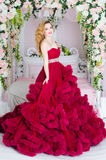 Woman in dress cloud burgundy. Charming woman in a beautiful lush dress cloud royal burgundy. She stands by the bed, decorated with flowers Stock Images