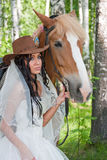 Woman in the dress of fiancee next to a horse Stock Photography
