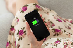 Woman in dress floral print holding phone with charged battery Stock Images