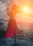 Woman in dress with glass of wine. Woman in a red dress with glass of red wine on a beach. Selective soft focus stock image