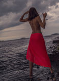 Woman in dress with glass of wine. Woman in a red dress with glass of red wine on a beach. Selective soft focus royalty free stock photography