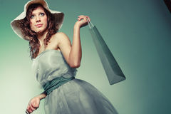 Woman in dress and hat hold shopping bag Stock Photos