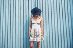Woman in dress with hat outside by blue fence stock image