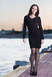 Woman in dress and high heels standing on waterfront Royalty Free Stock Image