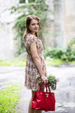 Woman in dress hold flowers and bag Stock Photography