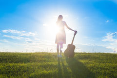Woman in dress holding the guitar on cloudy sunset sky Stock Photography
