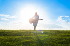 Woman in dress holding the guitar on cloudy sunset sky Royalty Free Stock Photo