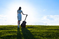 Woman in dress holding the guitar on cloudy sunset sky Royalty Free Stock Images