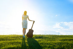 Woman in dress holding the guitar on cloudy sunset sky Stock Photos