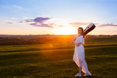 Woman in dress holding the guitar on cloudy sunset sky Royalty Free Stock Image