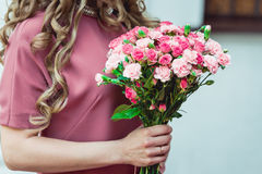 Woman in a dress holding wedding bouquets of biege carnations and pink roses stock photo