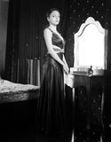 Woman in Dress Inside her Room Looking at Camera. Woman in Long Dress Standing Inside her Room, Looking at Camera. Captured in Monochrome Style Royalty Free Stock Image
