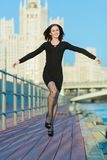 Woman in dress jumping arms outstretched to the sides Stock Photos