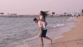 Woman in dress jumps on boyfriend back at water slow motion. Smiling woman in short dress jumps on boyfriend back in surf line of calm ocean on day slow motion stock video