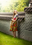 Woman in dress leaning against old chinese brick wall Royalty Free Stock Photography