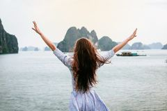 Woman look on HALONG bay in Vietnam and rise hands. UNESCO World Heritage Site. Woman in dress with long hair look on HALONG bay in Vietnam and rise hands stock photography