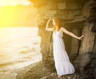 Woman in dress looking to the sea. Stock Photo