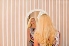 Woman in a dress looks in the mirror Royalty Free Stock Images