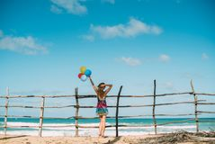 Woman in a dress looks at ocean. Holds balloons in hand. Horizon stock image