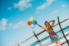 Woman in a dress looks at ocean. Holds balloons in hand stock photo