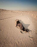 Woman in dress lying on sand dune at desert Stock Photos