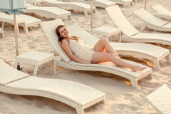 Woman in dress lying on sunbed at empty beach Stock Images