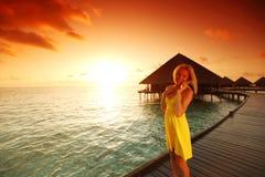 Woman in a dress on maldivian sunset stock photo