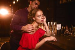 Woman in dress and man behind bar counter, flirt Stock Photo