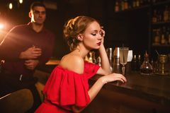 Woman in dress and man behind bar counter, flirt. Woman in red dress, men behind bar counter, flirt. Date in nightclub, attractive couple in pub stock photo