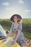 Woman in dress with map near a yellow car Stock Photos