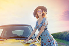 Woman in dress with map near a yellow car Royalty Free Stock Image