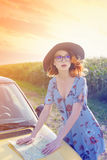 Woman in dress with map near a yellow car Royalty Free Stock Photos