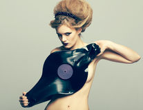 Woman in dress of molten vinyl disk Royalty Free Stock Images