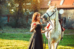 Woman in dress next to the horse. Portrait attractive woman full length next horse Stock Photo