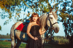 Woman in dress next to the horse. Portrait attractive woman full length next horse Stock Image