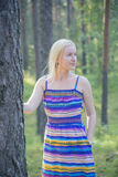 Woman in dress next to tree stem Stock Photo