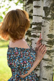 Woman in a dress with open shoulders is about Birch Stock Images