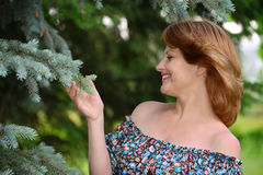 Woman in a dress with open shoulders at pine forest. A woman in a dress with open shoulders in a pine forest stock photos
