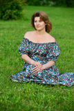 Woman in a dress with open shoulders sitting on the grass Stock Images