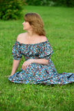 Woman in a dress with open shoulders sitting on the grass Royalty Free Stock Photo